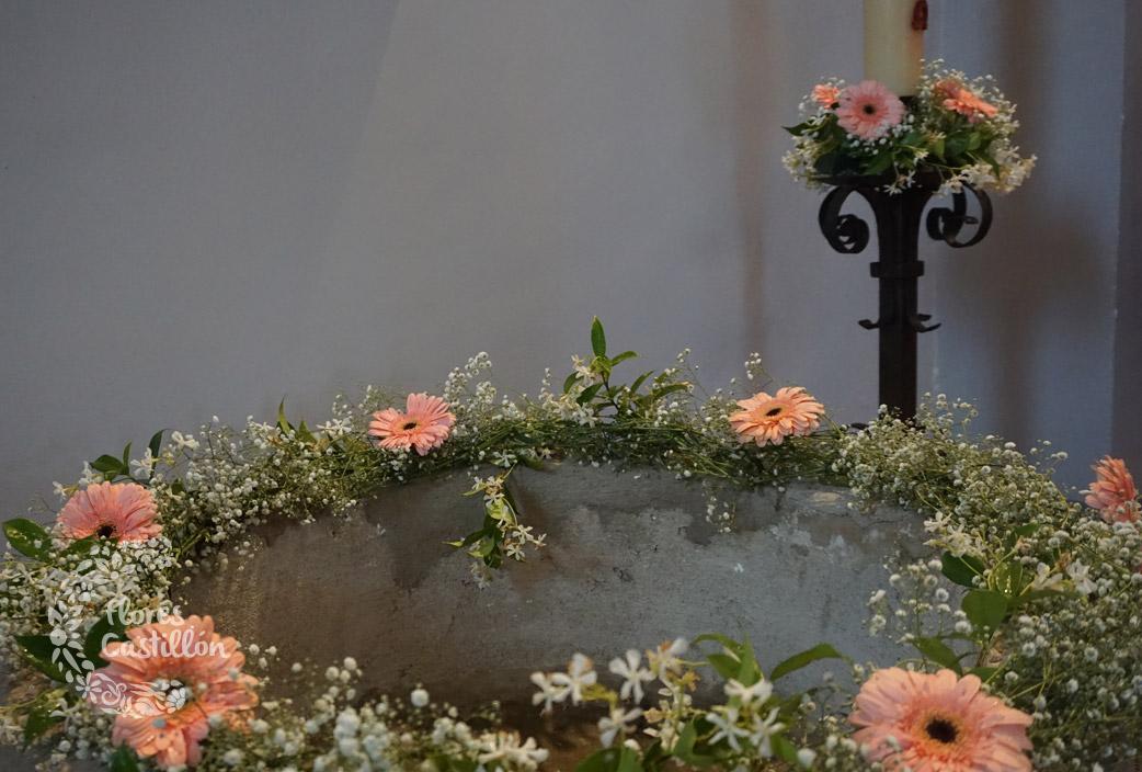 guirnalda de flores pila bautismal y cirio